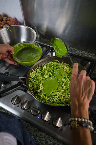 zucchini noodles are cooking in a skillet and a hand is adding green sauce as they cook