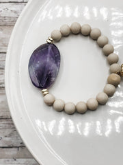 Amethyst Wrist Art features a singular amethyst bead, frosted jasper and gold accents. Hidden within the design is a white wood bead should you choose to difuse essential oils.