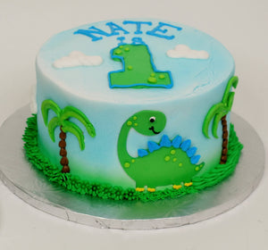 MaArthur's Bakery Custom Cake With Number 1 on Top and Green Dinasour and Palm Trees on Sides