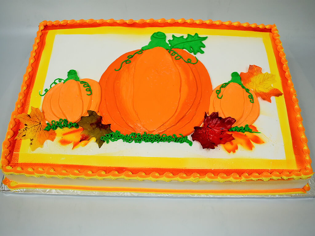 McArthur's Bakery Custom Cake with Fall Theme of Large Orange Pumpkin and Pumpkin Field