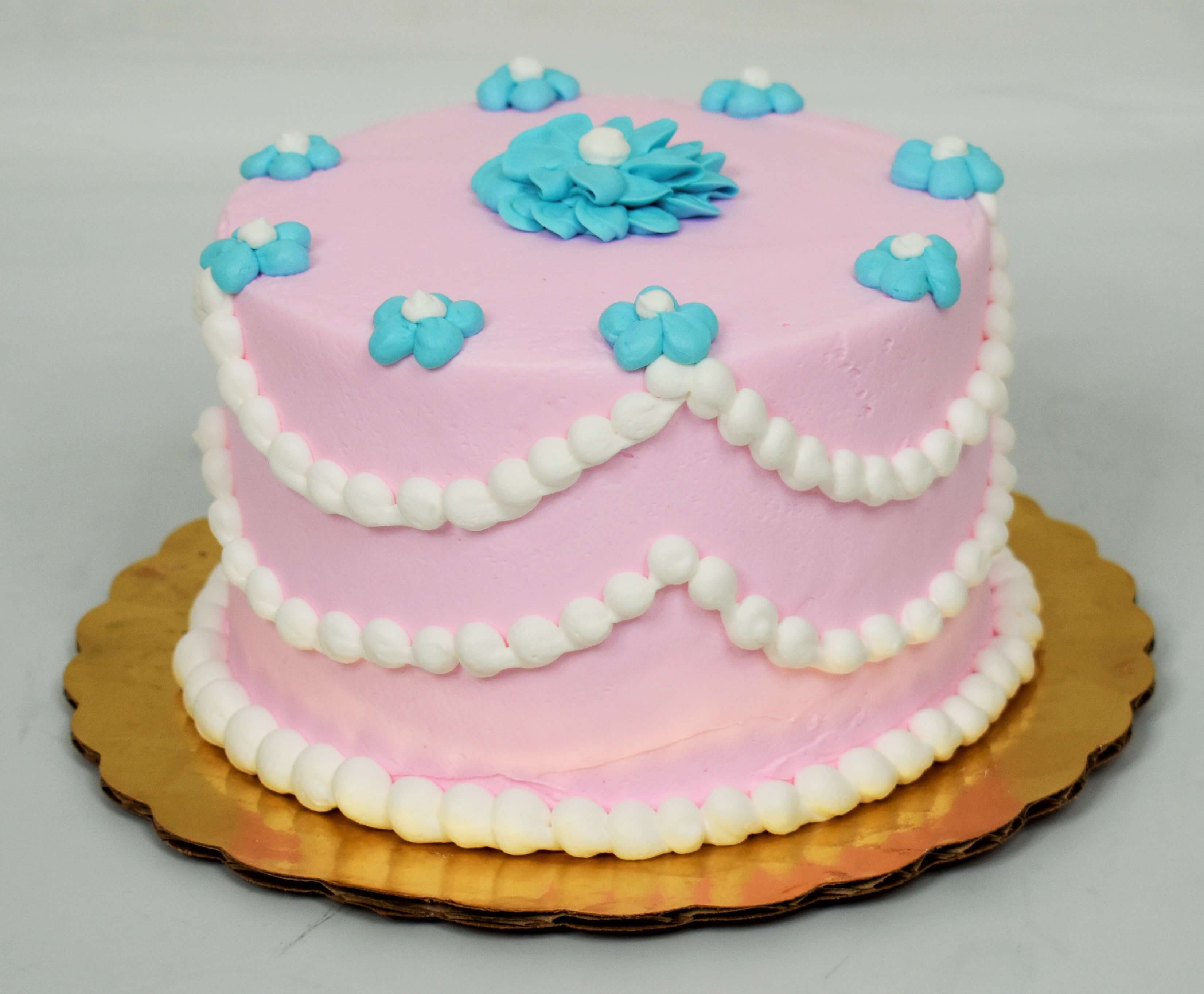 MaArthur's Bakery Custom Cake with Pink Background, White Beaded Draping, and Blue Flowers