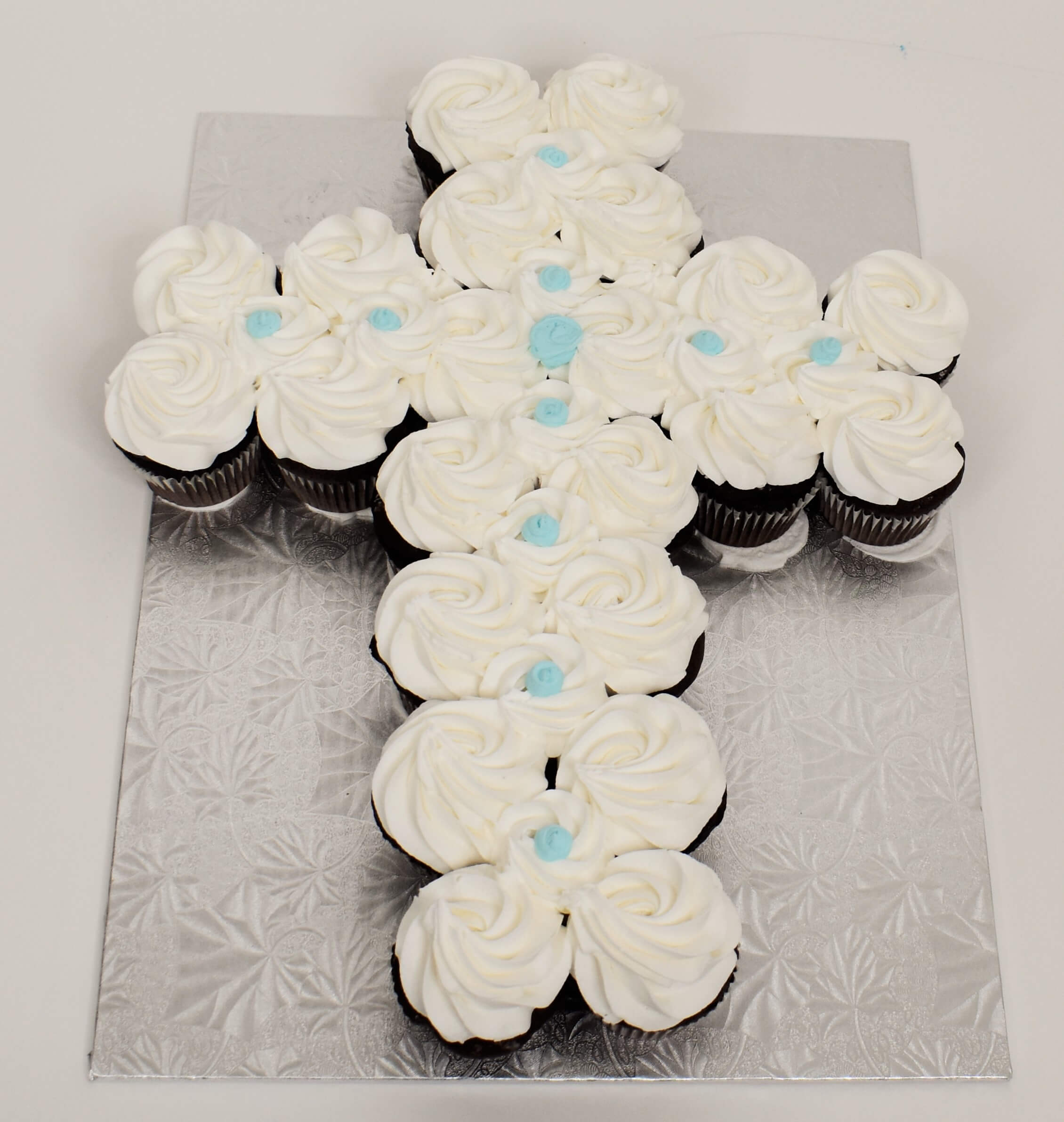 McArthur's Bakery Cupcake Cake In the shape of a cross with white and blue icing.