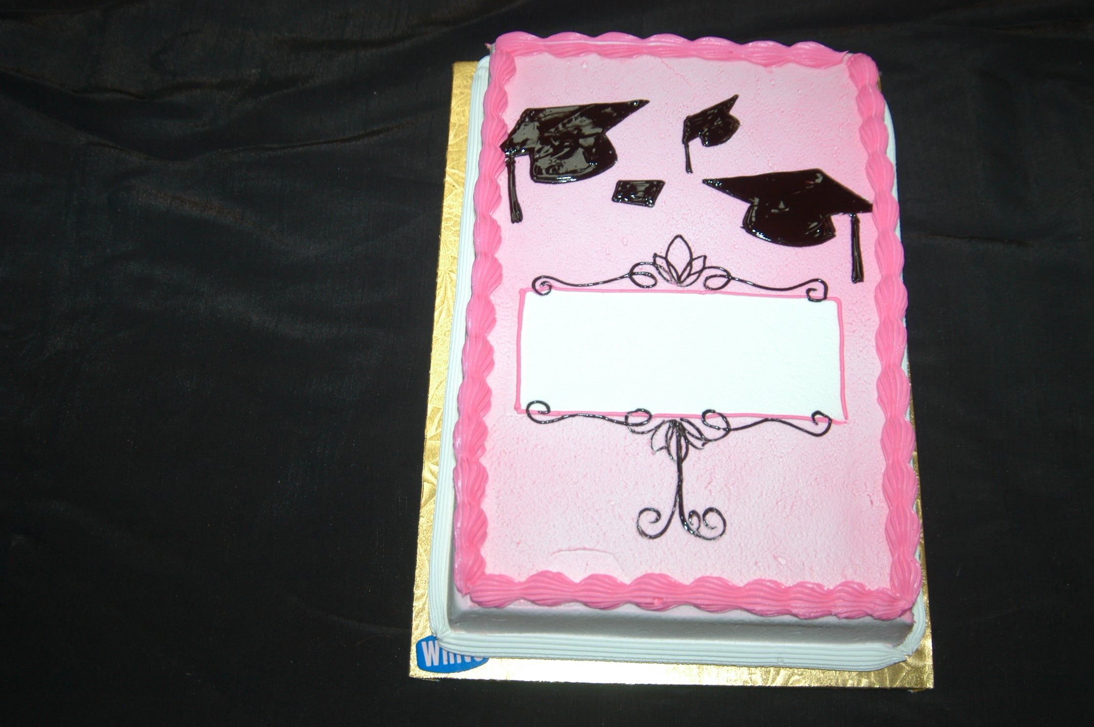 MaArthur's Bakery Custom Cake with Pink Background and Black Gradutation Caps