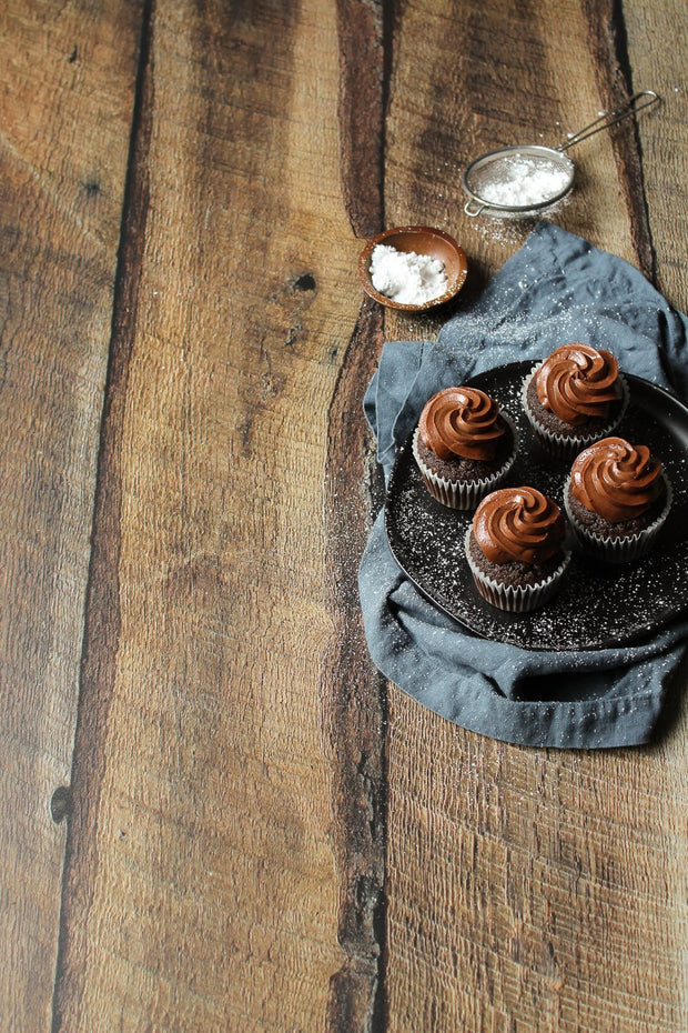 Super-Thin & Pliable Dark Brown Reclaimed Barn Wood Replica Photography Backdrop 2 ft x 3ft, Lightweight, Moisture & Stain-Resistant with chocolate cupcakes on a plate with a blue napkin
