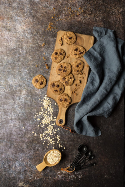Super-Thin & Pliable Cookie Sheet Photography Backdrop 2 ft x 3 ft, Lightweight, Moisture & Stain-Resistant with cookies on a wooden board