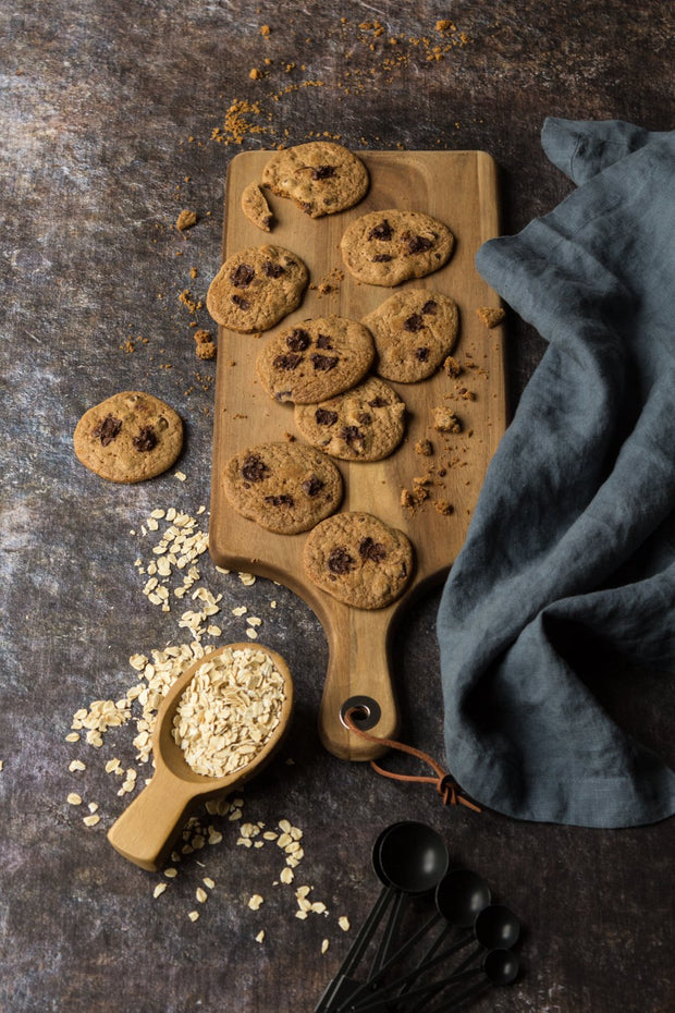 Super-Thin & Pliable Cookie Sheet Photography Backdrop 2 ft x 3 ft, Lightweight, Moisture & Stain-Resistant with chocolate chip cookies on a cutting board