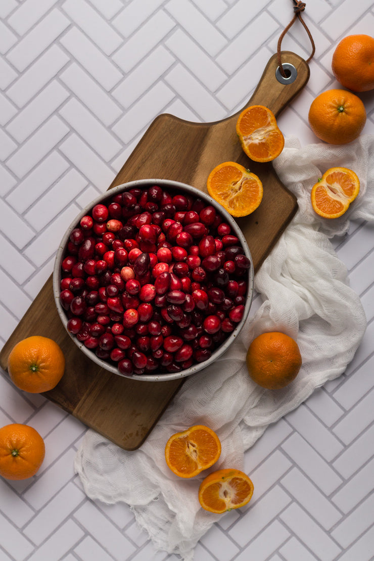 Chevron Tile Replica Photography Backdrop with a bowl of cranberries and oranges on a wooden board