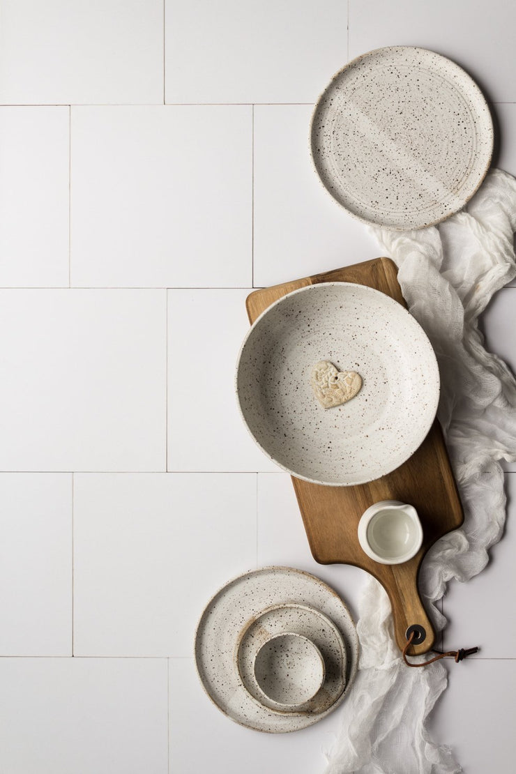 White pottery plates and bowls on a wooden cutting board on the Super-Thin & Pliable Creamy White Tile Replica Photography Backdrop
