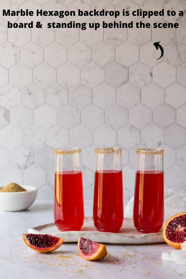 Glasses of red soda with blood oranges with a Super-Thin Marble Hexagon Tile Replica Photography Backdrop