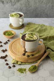 Two cups of matcha hot chocolate with chocolate chips on a Super-Thin Marble Hexagon Tile Replica Photography Backdrop