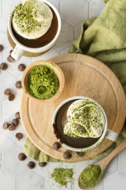 Matcha hot chocolate in mugs with matcha powder on a wooden board on a Marble Hexagon Tile Replica Photography Backdrop