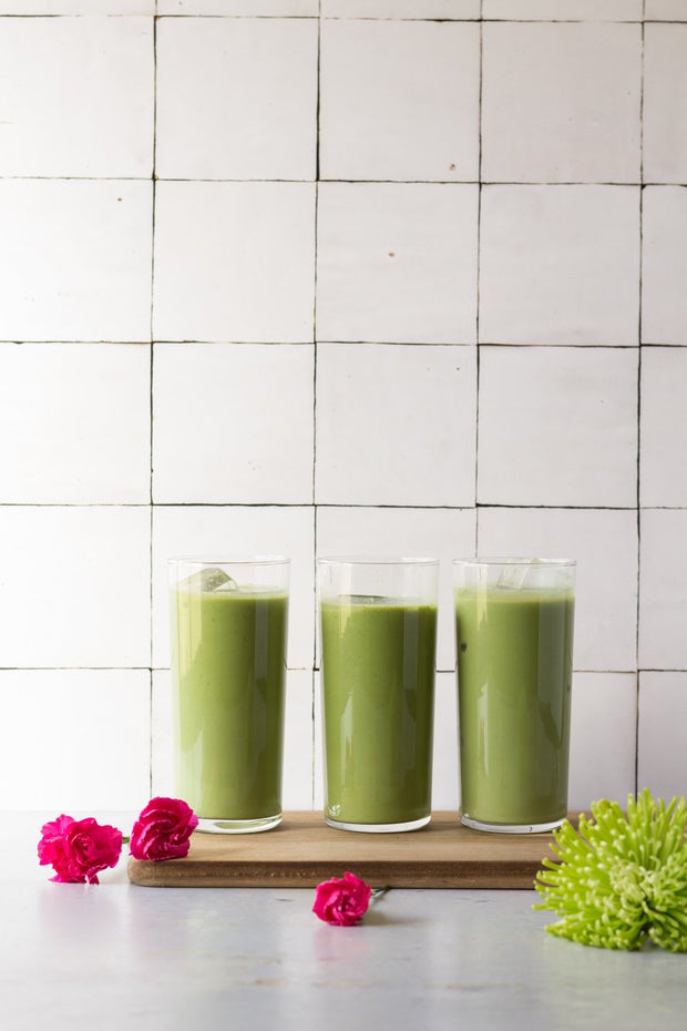 Three green matcha drinks in glasses with a Moroccan Tile Replica Photography Backdrop
