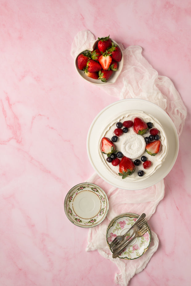 Super-Thin & Pliable Pink Marble Photography Backdrop 2 ft x 3 ft, Lightweight, Moisture & Stain-Resistant with a cake with strawberries