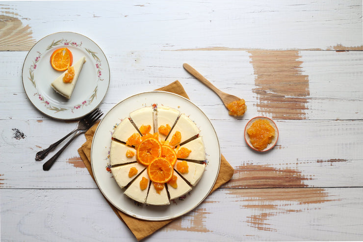 Super-Thin & Pliable Whitewashed Reclaimed Wood Replica Photography Backdrop 2 ft x 3 ft, Lightweight, Moisture & Stain-Resistant with an orange marmalade and cheesecake