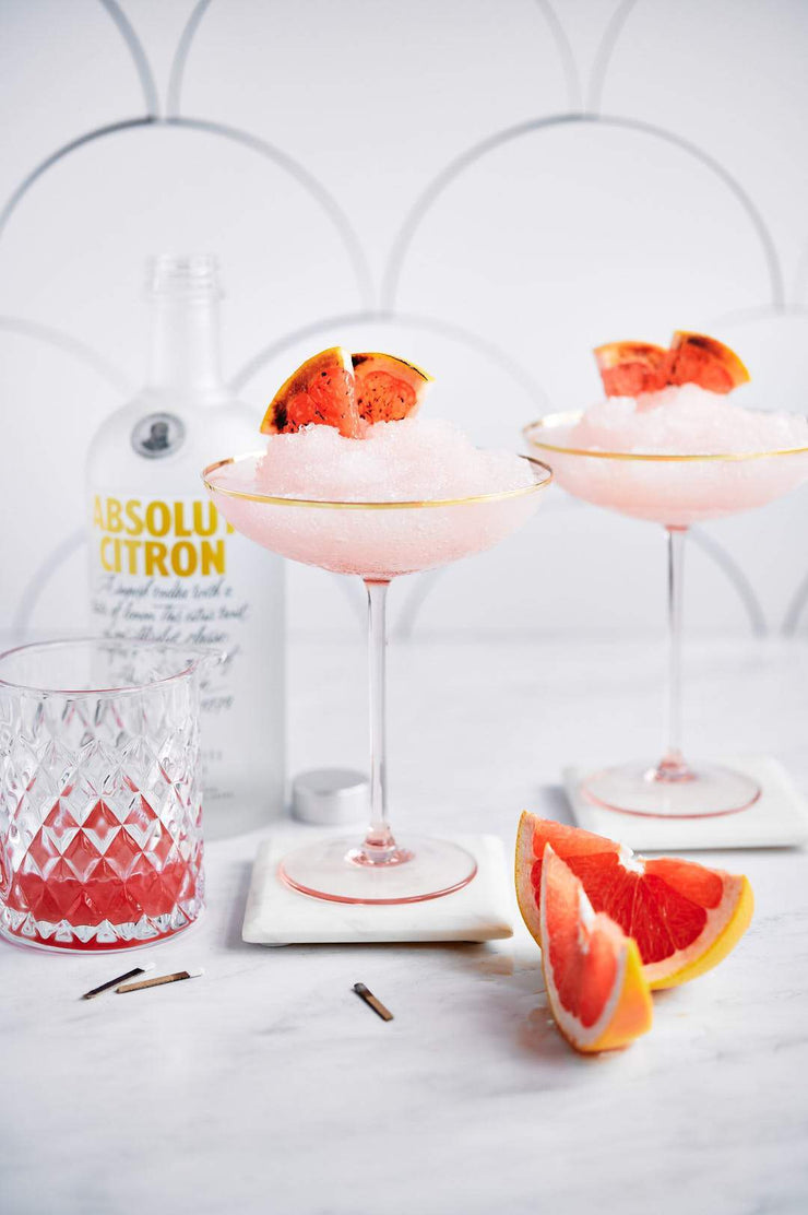 Two pink ice drinks in glasses with oranges and vodka with a Super-Thin & Pliable Scalloped Tiles Replica Photography Backdrop