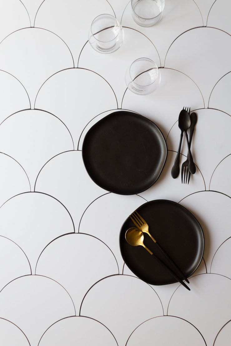 Black plates and black forks and spoons on a Super-Thin & Pliable Scalloped Tiles Replica Photography Backdrop