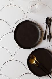 Black plates with spoons and forks on a Super-Thin & Pliable Scalloped Tiles Replica Photography Backdrop