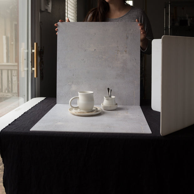 20-inch x 20-inch Soft Concrete Photography Backdrop 3 mm thick Physical Board, Lightweight, Moisture & Stain-Resistant with a person holding them up
