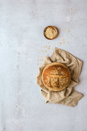 Soft Concrete Photography Backdrop Board 2 ft x 3 ft | 3 mm thick board with a loaf of bread, oats, and linen napkins