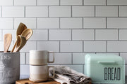 Super-Thin & Pliable Most Realistic Subway Tile Photography Backdrop 3ft x 2 ft Lightweight, Moisture & Stain-Resistant with a bread box, cups, and wooden spoons
