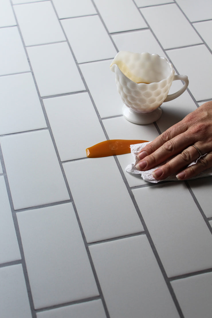 The Most Realistic Subway Tile Photography Backdrop 3ft x 2 ft | 3 mm thick with a spill being wiped clean