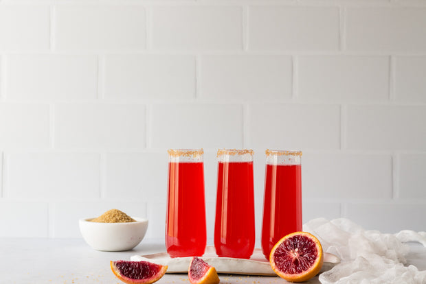 Subway Tile with White Grout Photography Backdrop  with three red sparkling drinks and blood oranges