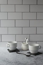 20-inch x 20-inch The Most Realistic Subway Tile Photography Backdrop 3 mm thick Physical Board, Lightweight, Moisture & Stain-Resistant with two coffee cups and a coffee creamer with spoons