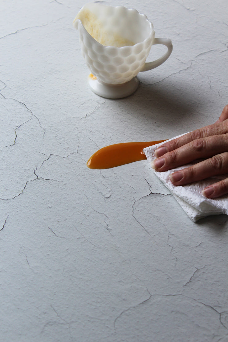 White Chipped Paint Photography Backdrop 2 ft x 3 ft | 3 mm thick with a spill being wiped clean