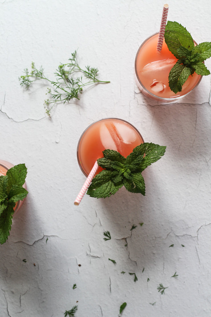 White Chipped Paint Photography Backdrop 2 ft x 3 ft | 3 mm thick with three glasses of grapefruit juice and sprigs of mint