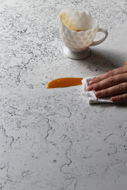 White Plaster Photography Backdrop 2 ft x 3 ft | 3 mm thick with a spill being wiped clean