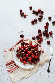 Super-Thin & Pliable White Plaster Photography Backdrop 2 ft x 3 ft, Lightweight, Moisture & Stain-Resistant with a plate of cherries
