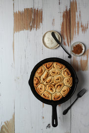 Whitewashed Reclaimed Wood Photography Backdrop 2 ft x 3 ft board | 3 mm thick with cinnamon rolls in a cast iron skillet