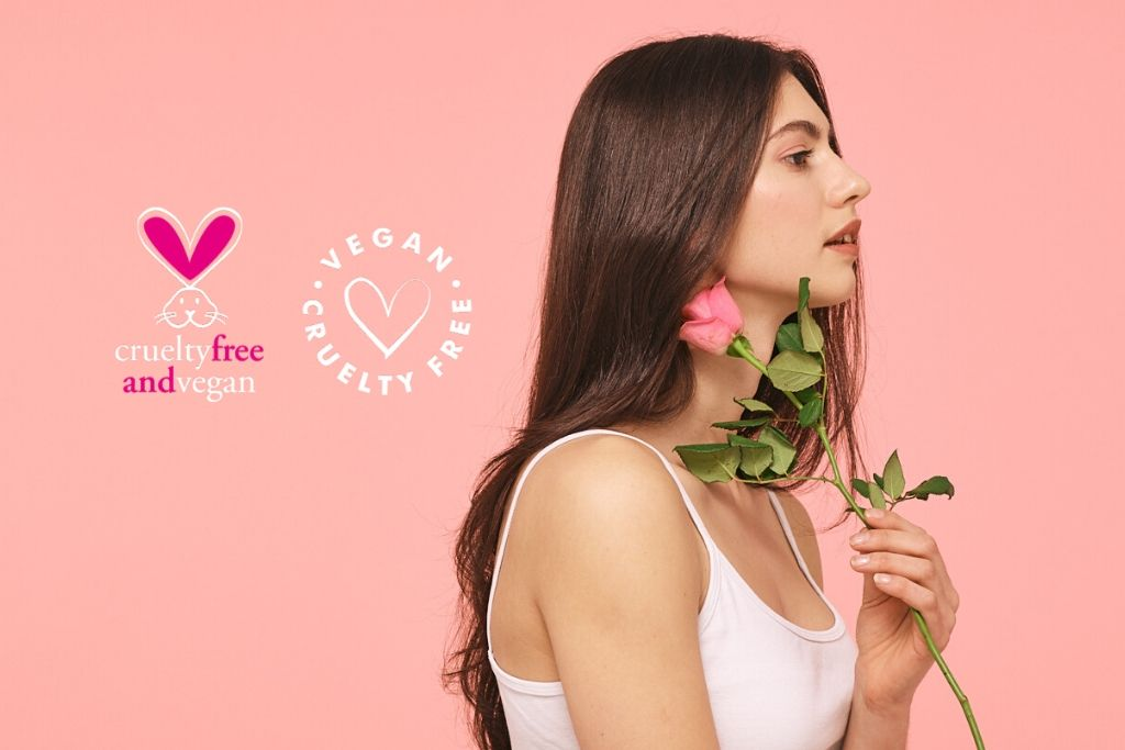 Vegan hair care. Brunette girl holding rose against pink background with cruelty free & vegan kigi,