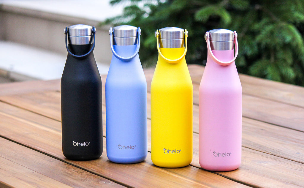 Ohelo plain bottles in black, blue, yellow and pink lined up on a wooden table