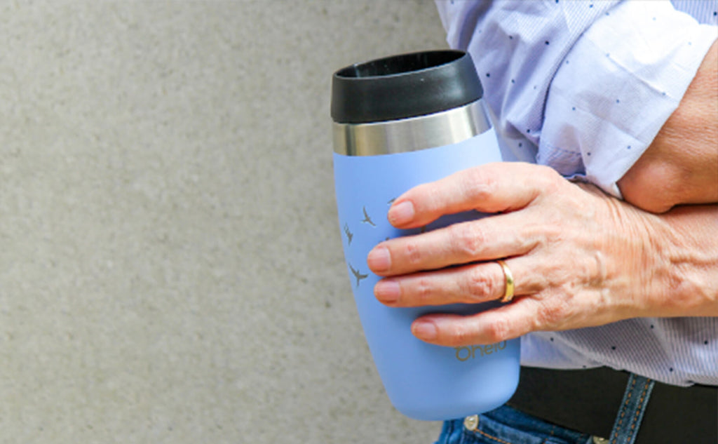 Ohelo blue swallows tumbler being held by a woman