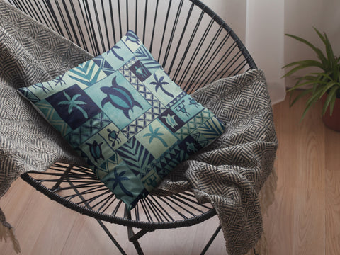 Blue Hawaiian Petroglyph accent pillow on a rattan chair