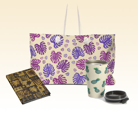 Purple tropical leaves weekender bag, Hawaiian petroglyph hardcover journal, and blue pineapples travel mug