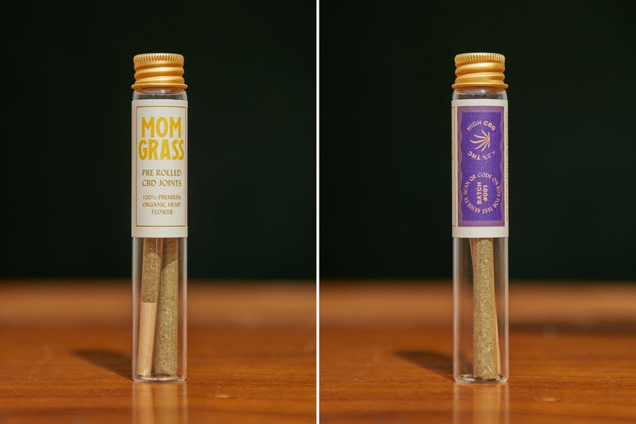 Two Mom Grass hemp CBG flower joints in a glass vial with Mom Grass label, front view and rear view