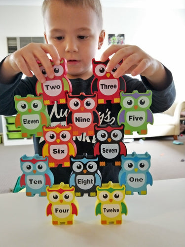 Stacking and balancing wooden owls with numbers on them