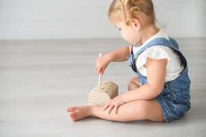 Girl playing with wooden worm catching game using magnetic stick to catch wooden coloured worms