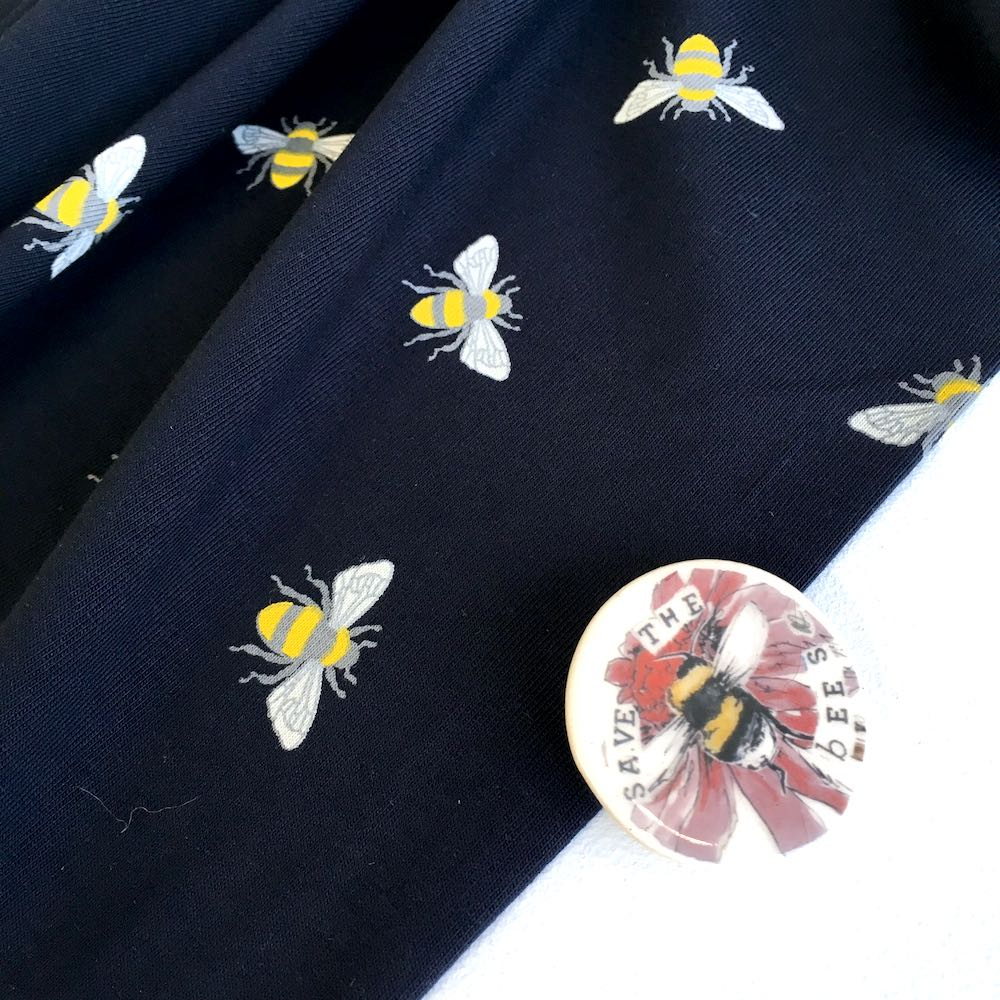 Scattered Bumble Bees Navy Stretch Jersey Print Fabric. Perfect for dresses, tops, tshirts and other sewing and dressmaking projects.