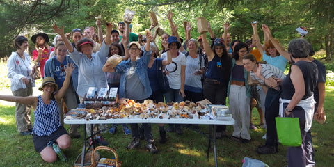 Participants at a Catskill Fungi mushroom walk gathered around a table covered with foraged mushrooms, and holding up mushrooms jubilantly.