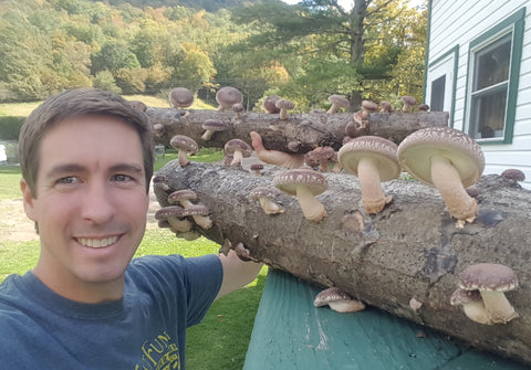 Catskill Fungi owner John Michelotti with cultivated Shiitake mushrooms growing on a log.