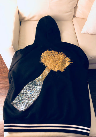 This is a picture of the hoodie that I designed with a hand-sewn sequin champagne bottle