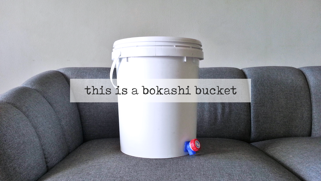 white bokashi bucket with faucet on grey surface