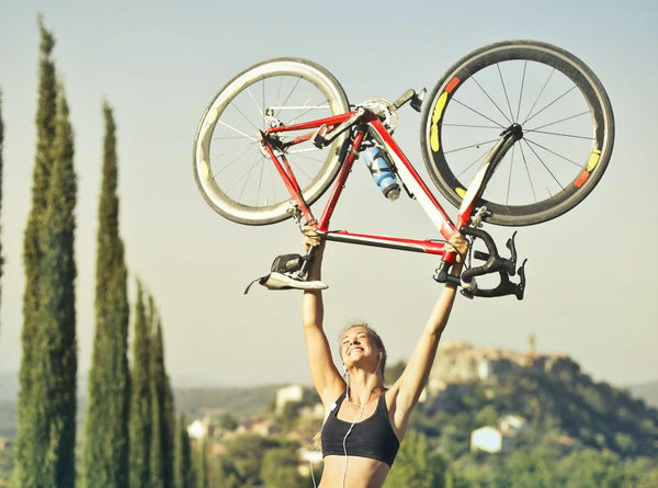 Girl holding up a bicycle