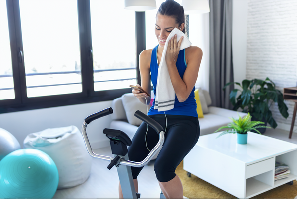 Woman at home on exercise bike