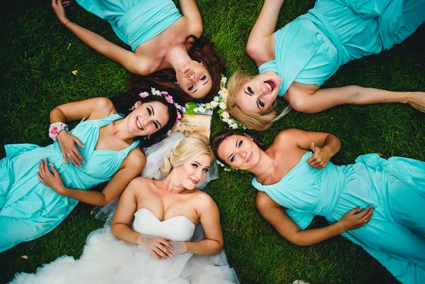 bride and bridesmaids lying in circle on lawn