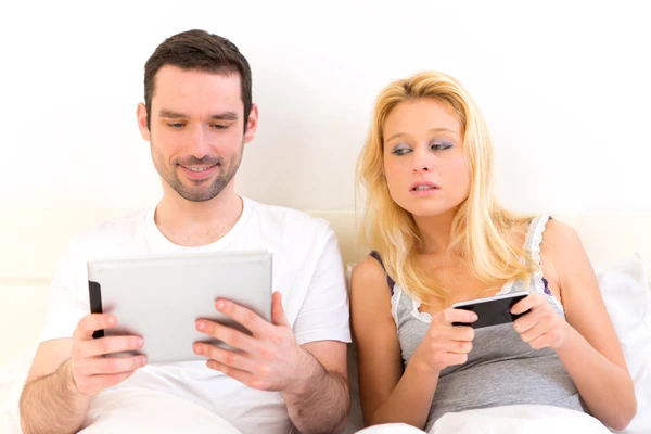 Couple playing with smartphones in bed