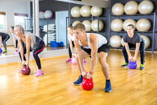 Focused group trains with kettlebells at fitness gym